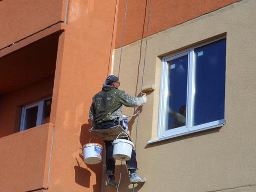 На изображении показан процесс покраски фасада