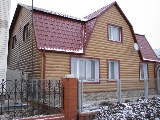 Фасад дома, обшитый металлическим блок-хаусом на картинке