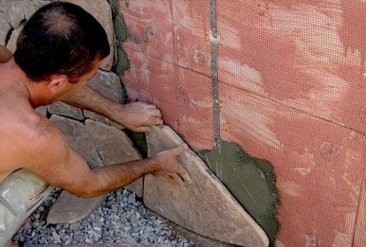 На фото показан процесс облицовки цоколя камнем