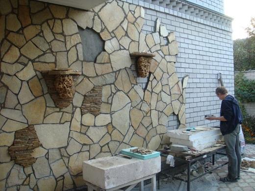 На фото показан процесс облицовки цоколя песчаником
