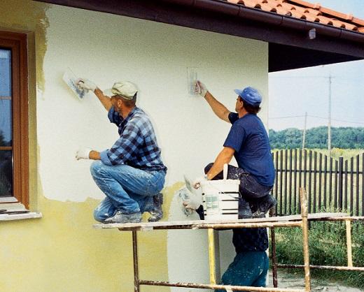 На фото показан процесс нанесения штукатурки на фасад