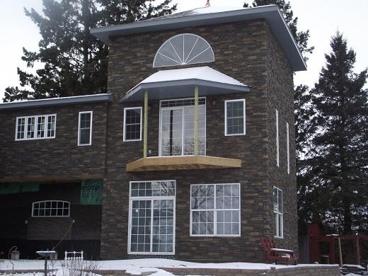 Фасад дома из черных панелей под камень