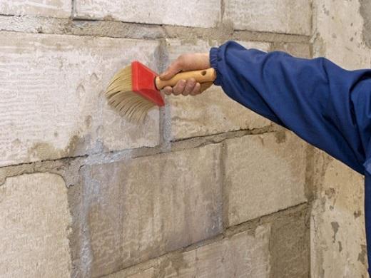 На фото показан процесс нанесения грунтовки на фасад