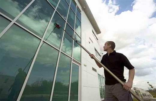 На снимке показан процесс мойки стеклянного фасада