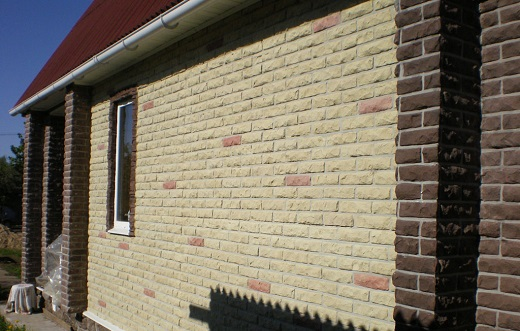 На фото фасад дома, облицованный панелями под камень