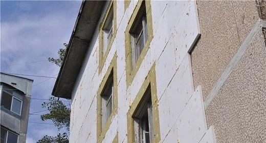 На снимке показан процесс утепления дома пенопластом