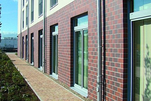 Облицовочная плитка для фасада под кирпич украшает первый этаж здания