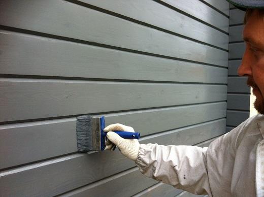 Нанесение краски на деревянный фасад на снимке