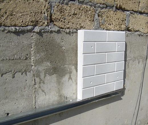 На фото показан процесс монтажа теплой плитки на фасад