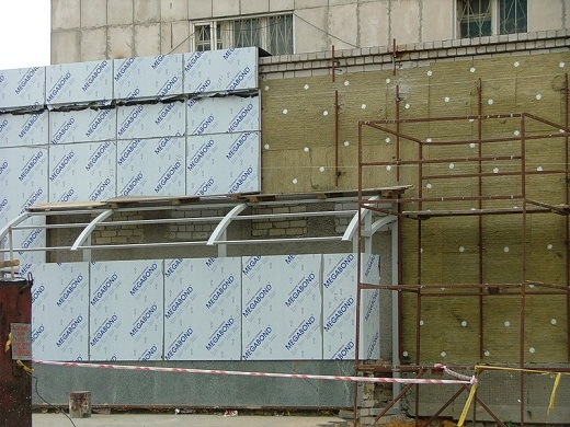 На снимке показан процесс устройства теплоизоляции фасада