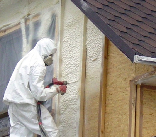 На изображении показан процесс напыления утеплителя на фасад дома