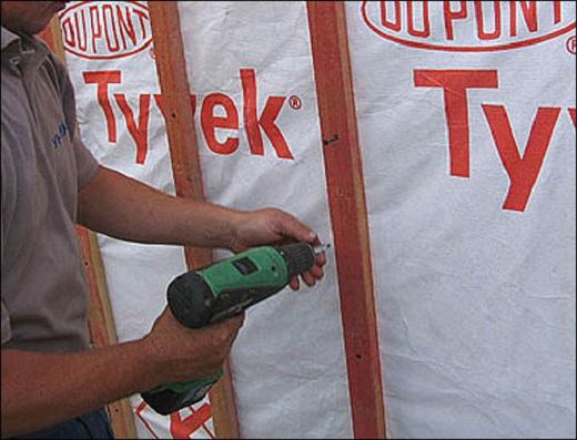 На фото показан процесс монтажа утеплителя и обрешетки на стены дома