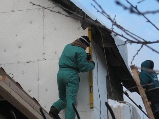 На фото показан процесс монтажа утеплителя на фасад дома