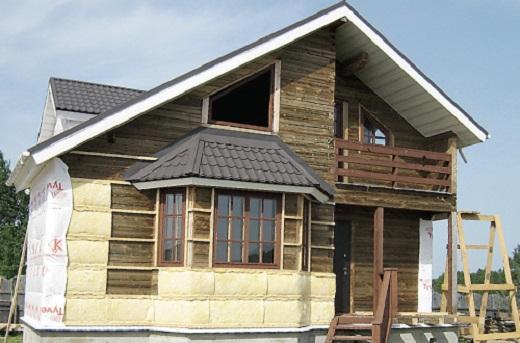 На снимке показан процесс монтажа вентилируемого фасада на деревянный дом